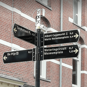 Amsterdams bewegwijzeringsbord op paal, met wapen van Amsterdam en richtingsindicator